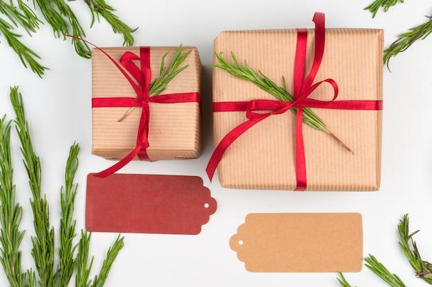 Geschenkdozen verpakt in kraftpapier met eenvoudig decor van groene plantentakken