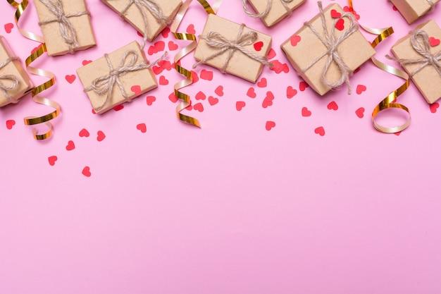 Geschenkdozen verpakt in kraftpapier op een roze achtergrond. confetti harten en gouden linten, feestelijk decor. plat ontwerp, bovenaanzicht