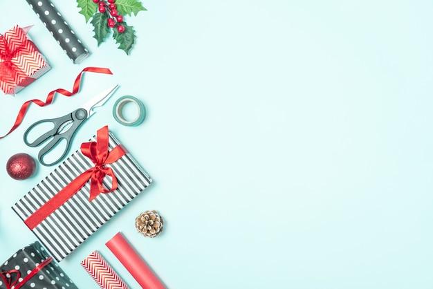 Geschenkdozen verpakt in zwart-wit gestreept en rood papier met inpakmateriaal op een blauwe achtergrond. kerstcadeautjes voorbereiding.