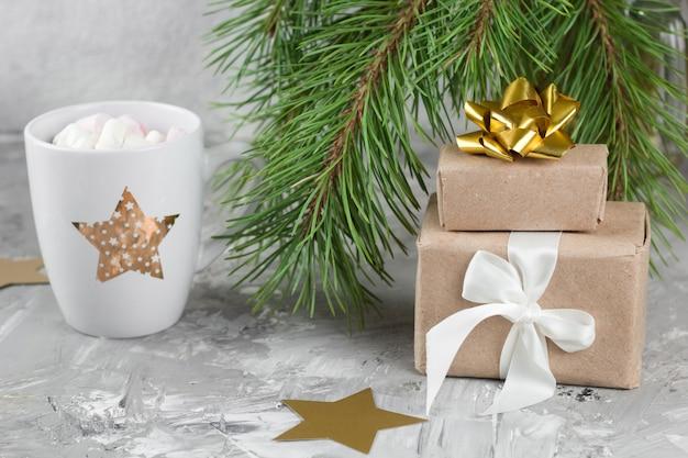 Geschenkdozen, warme drank met marshmallows, shabby grijze achtergrond met kerstboom takken