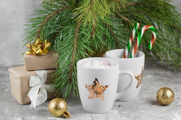 Geschenkdozen, warme drank met marshmallows, snoep stokken en gouden ballen op shabby grijze achtergrond