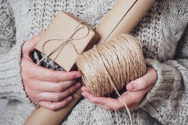Geschenken, ambachtelijk papier, een rol touw in vrouwenhanden, close-up. handgemaakte geschenken concept. moderne trend, natuurlijke geschenkverpakkingen. vakantie achtergrond.