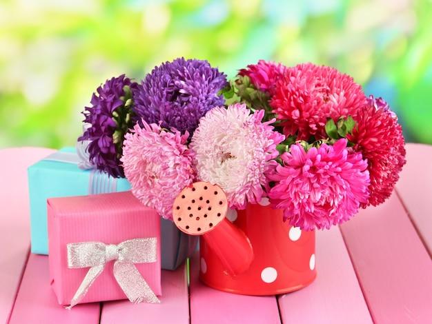 Geschenken en bloemen in gieter, op natuur achtergrond