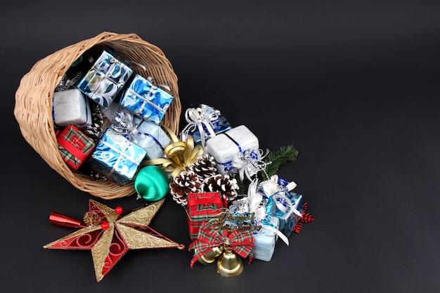 Geschenken en decoraties in een mand van kerstmis met een zwarte achtergrond.