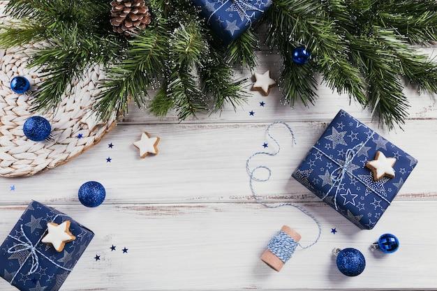 Geschenken, fir tree takken, blauwe decoraties op houten