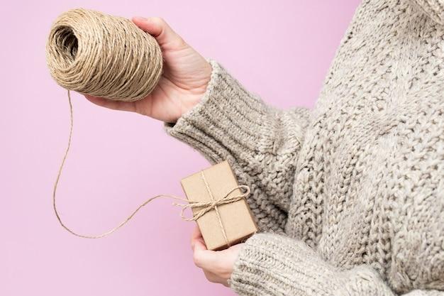 Geschenken gemaakt van kraftpapier, een rol touw in vrouwenhanden op een roze achtergrond, close-up. handgemaakte geschenken concept. moderne trend, natuurlijke cadeauverpakking met je eigen handen. vakantie achtergrond.