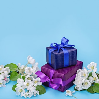 Geschenken in blauw en paars papier, witte bloemen van appelboom.