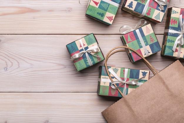 Geschenken in dozen, verpakt in papier met kerst- en nieuwjaarsfoto's. pakket voor dozen op een lichte houten tafel.