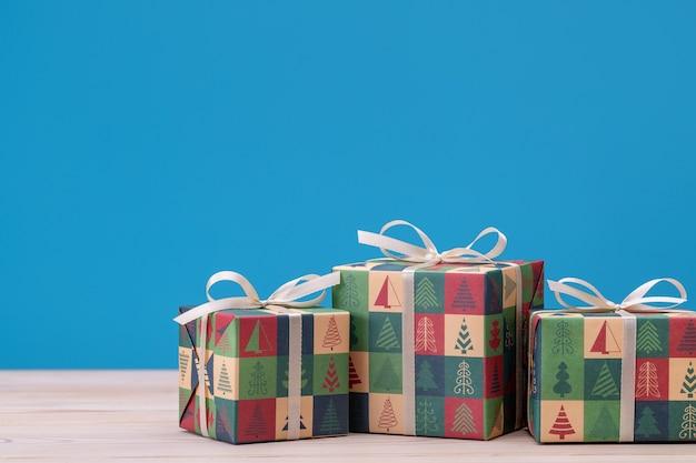 Geschenken in dozen, verpakt in papier met kerst- en nieuwjaarsfoto's. vakantiesouvenirs op blauwe muur.