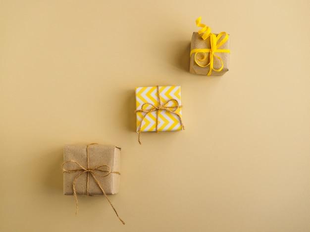 Geschenken in gele stijl op gele ondergrond. geschenken verpakt in kraftpapier