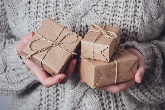 Geschenken in handen van vrouwen, close-up. monochroom, minimalistisch cadeauconcept. een meisje in een trui houdt geschenkdozen van kraftpapier vast, vastgebonden met een touwtje. verrassingsachtergrond, wenskaart.