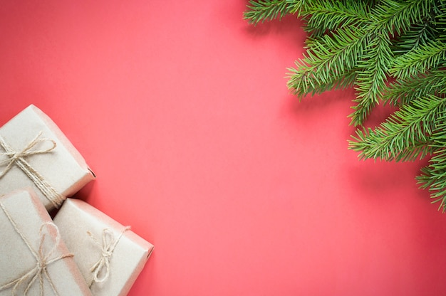 Geschenken in milieuvriendelijke ambachtelijke verpakking voor de vakantie en sparren op een rode achtergrond met kopie ruimte.