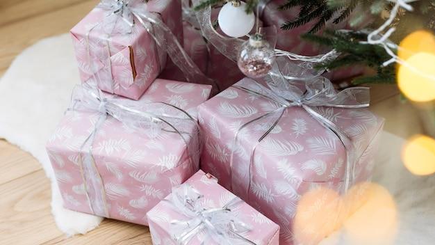 Geschenken in roze verpakking onder de kerstboom met een zilveren lint kerstmis en nieuwjaar