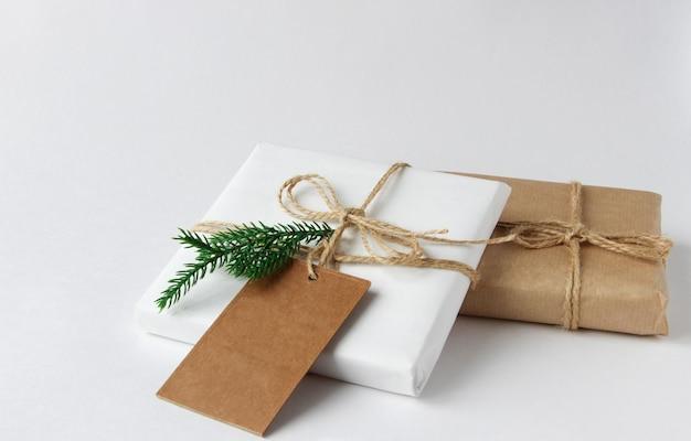 Geschenken in wit en ambachtelijk papier op een witte tafel met een sparrentak voorbereiding voor kerstmis