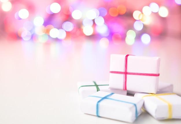 Geschenken in witte verpakking vastgebonden met veelkleurige linten tegen de achtergrond van onscherpe lichten