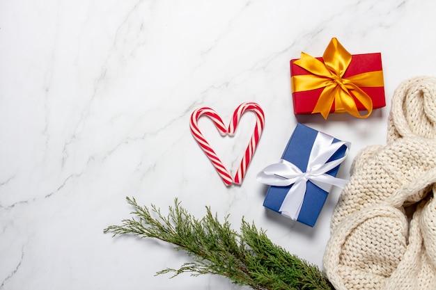 Geschenken, karamelriet, gebreide sjaal, vuren tak op een marmeren achtergrond.