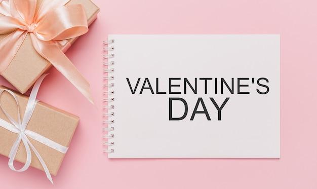 Geschenken met nota brief op geïsoleerde roze achtergrond, liefde en valentijn concept met tekst valentijnsdag