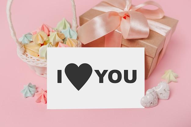 Geschenken met nota brief op geïsoleerde roze achtergrond met snoep, liefde en valentijn concept met tekst ik hou van jou