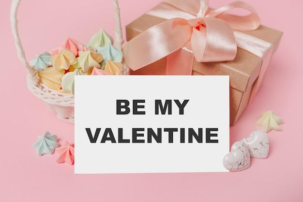 Geschenken met notitie brief op geïsoleerde roze achtergrond met snoep, liefde en valentijn concept met tekst wees mijn valentijn