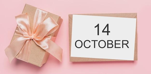 Geschenken met notitiebrief op geïsoleerd roze oppervlak, liefde en valentijnsconcept met tekst 14 oktober