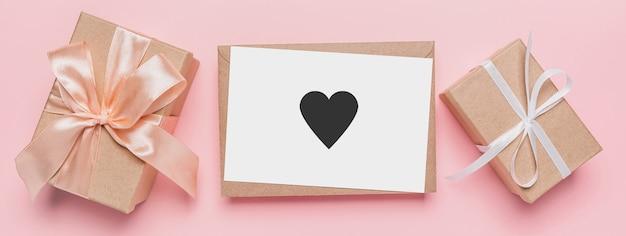 Geschenken met notitiebrief op geïsoleerde roze achtergrond, liefde en valentijnsconcept met hart