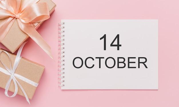 Geschenken met notitiebrief op geïsoleerde roze achtergrond, liefde en valentijnsconcept met tekst 14 oktober