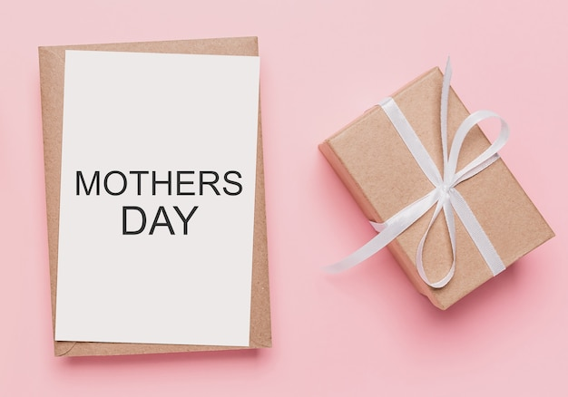 Geschenken met notitiebrief op geïsoleerde roze achtergrond, liefde en valentijnsconcept met tekst moederdag
