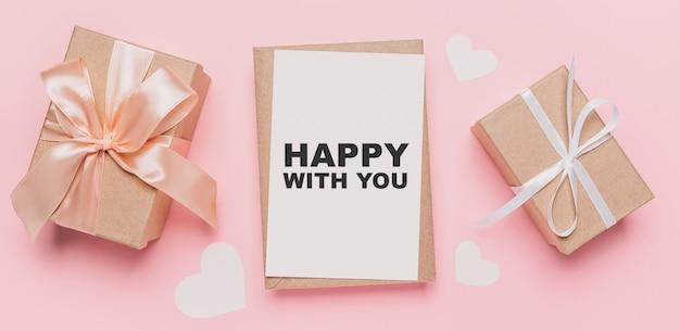 Geschenken met notitiebrief op geïsoleerde roze achtergrond, liefde en valentijnskaartconcept met tekst gelukkig met u