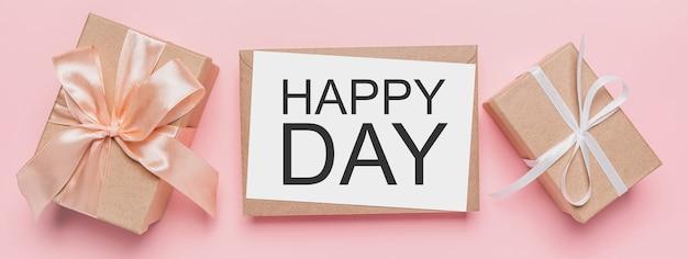 Geschenken met notitiebrief op geïsoleerde roze achtergrond, liefde en valentijnskaartconcept met tekst gelukkige dag