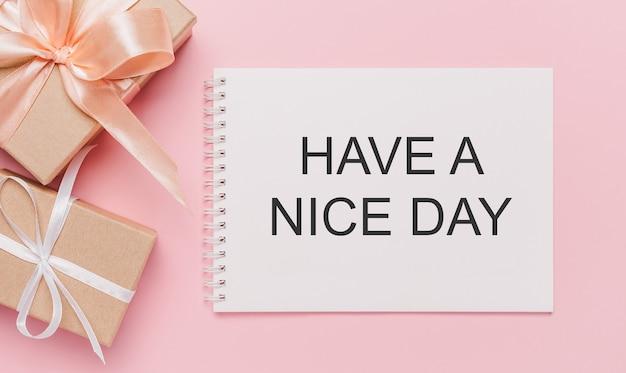 Geschenken met notitiebrief op geïsoleerde roze achtergrond, liefde en valentijnskaartconcept met tekst have a nice day