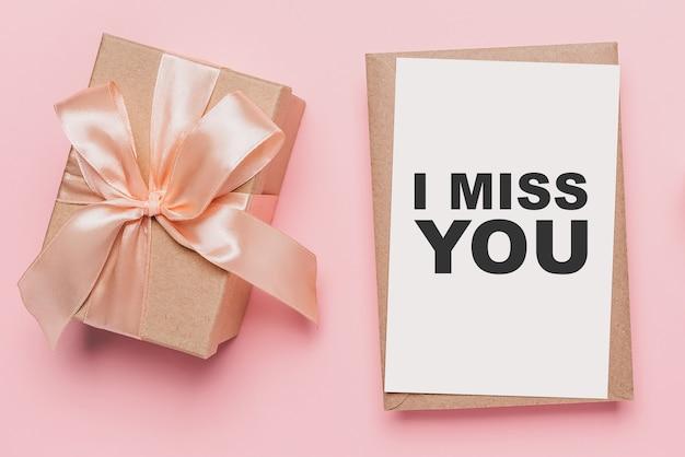 Geschenken met notitiebrief op geïsoleerde roze achtergrond, liefde en valentijnskaartconcept met tekst ik mis je