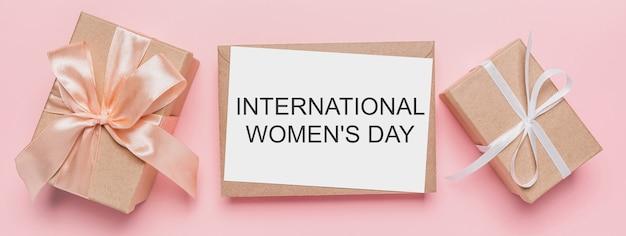 Geschenken met notitiebrief op geïsoleerde roze achtergrond, liefde en valentijnskaartconcept met tekst internationale vrouwendag