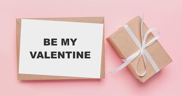 Geschenken met notitiebrief op geïsoleerde roze achtergrond, liefde en valentijnskaartconcept met tekst wees mijn valentijn