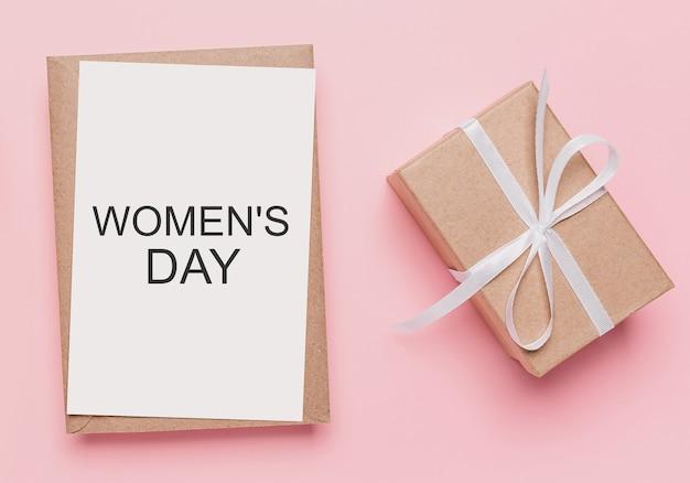 Geschenken met notitiebrief op geïsoleerde roze achtergrond, liefde en valentijnskaartconcept met tekst womens day