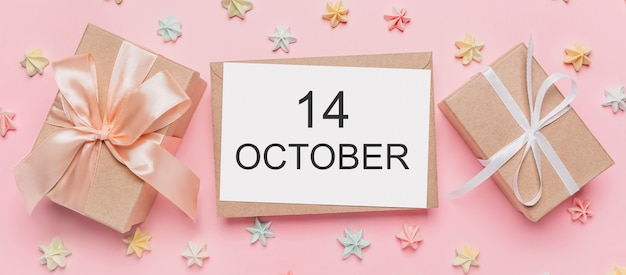 Geschenken met notitiebrief op geïsoleerde roze achtergrond met snoep, liefde en valentijnsconcept met tekst 14 oktober 14