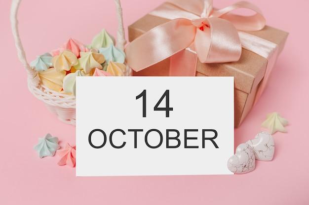 Geschenken met notitiebrief op geïsoleerde roze achtergrond met snoep, liefde en valentijnsconcept met tekst 14 oktober