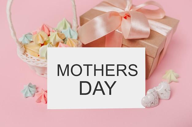 Geschenken met notitiebrief op geïsoleerde roze achtergrond met snoep, liefde en valentijnsconcept met tekst moederdag