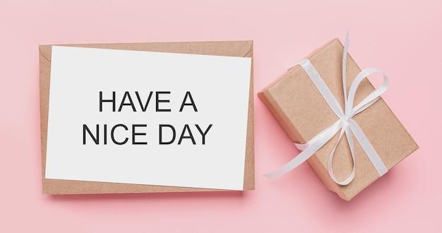 Geschenken met notitiebrief op geïsoleerde roze ondergrond met tekst hebben een mooie dag