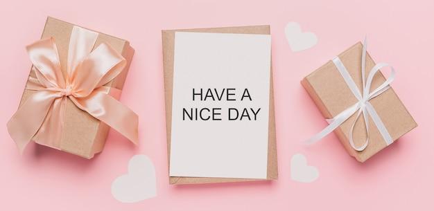 Geschenken met notitiebrief op geïsoleerde roze ruimte, liefde en valentijnskaartconcept met tekst have a nice day