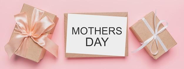 Geschenken met notitiebrief op geïsoleerde roze ruimte, liefde en valentijnskaartconcept met tekst moederdag