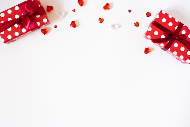 Geschenken met satijnen lint en strikken, confetti, steentjes, glazen harten op een lichte achtergrond. het concept van valentijnsdag