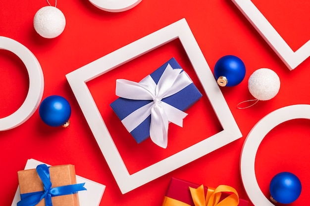Geschenken, podium en kerstspeelgoed op een rode achtergrond. bovenaanzicht, plat gelegd.