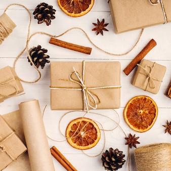 Geschenken van ambachtelijk papier, gedroogde sinaasappel, kaneel, dennenappels, anijs op een witte tafel het originele decor voor kerstmis.