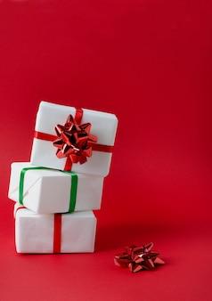 Geschenken verpakt in wit papier staan op elkaar, gebonden met rode en groene linten op een felrode verticale achtergrond met kopie ruimte