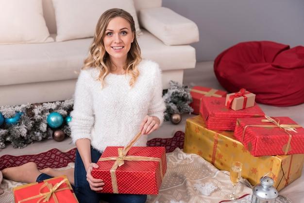 Geschenken voor kerstmis. charmante aardige opgetogen vrouw zit onder geschenkdozen en lacht tijdens het uitpakken van haar cadeau