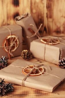Geschenken voor kerstmis en nieuwjaar. verpakte ambachtelijke geschenken met kaneel en sinaasappel ter decoratie.