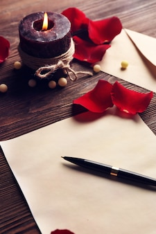 Geschenkenkaart voor valentijnsdag met pen, rode bloemblaadjes en kaars op houten oppervlak