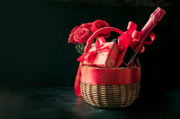 Geschenkmand, boeket rode rozen, fles champagne op zwart.