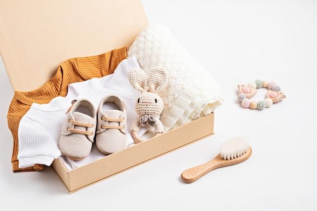 Geschenkmand met genderneutrale babykleding en accessoires. verzorgingsdoos van biologische pasgeboren katoenen kleding, mode, branding, idee voor een klein bedrijf. platliggend, bovenaanzicht