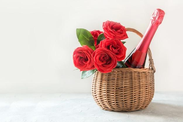 Geschenkpakket, boeket rode rozen, fles champagne op wit. valentijnsdag kaart. romantisch cadeau.